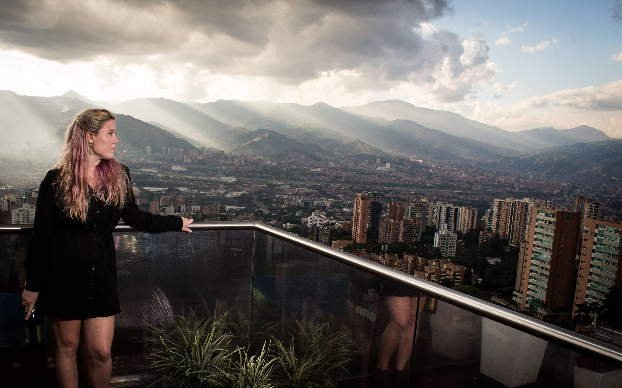 Woman standing on balcony overlooking stormy Medellin sky.
