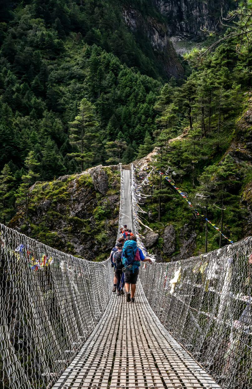 hiking on a suspension bridge in Nepal