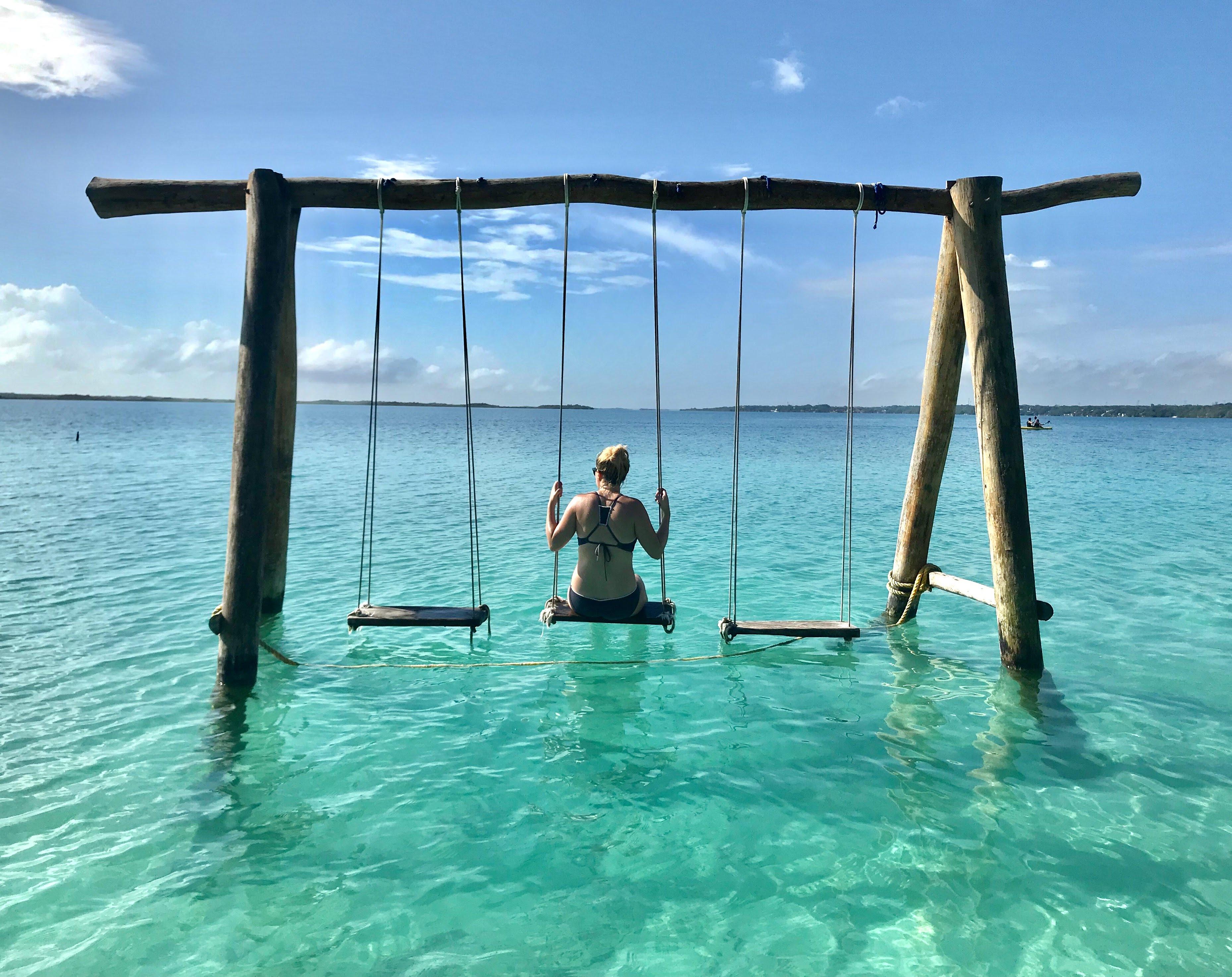 girl on water swings in laguna bacalar