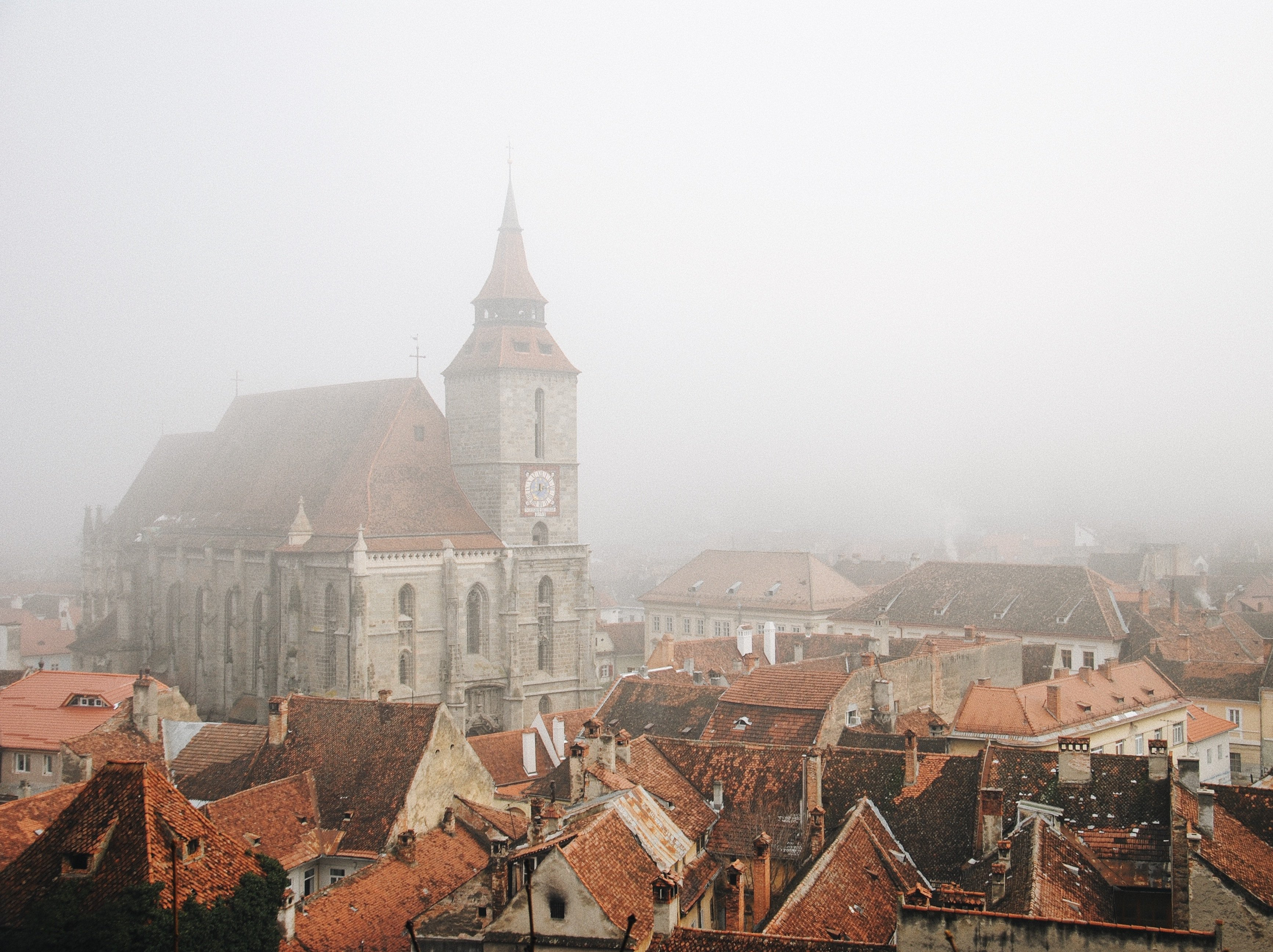 romanian church and old town under fog