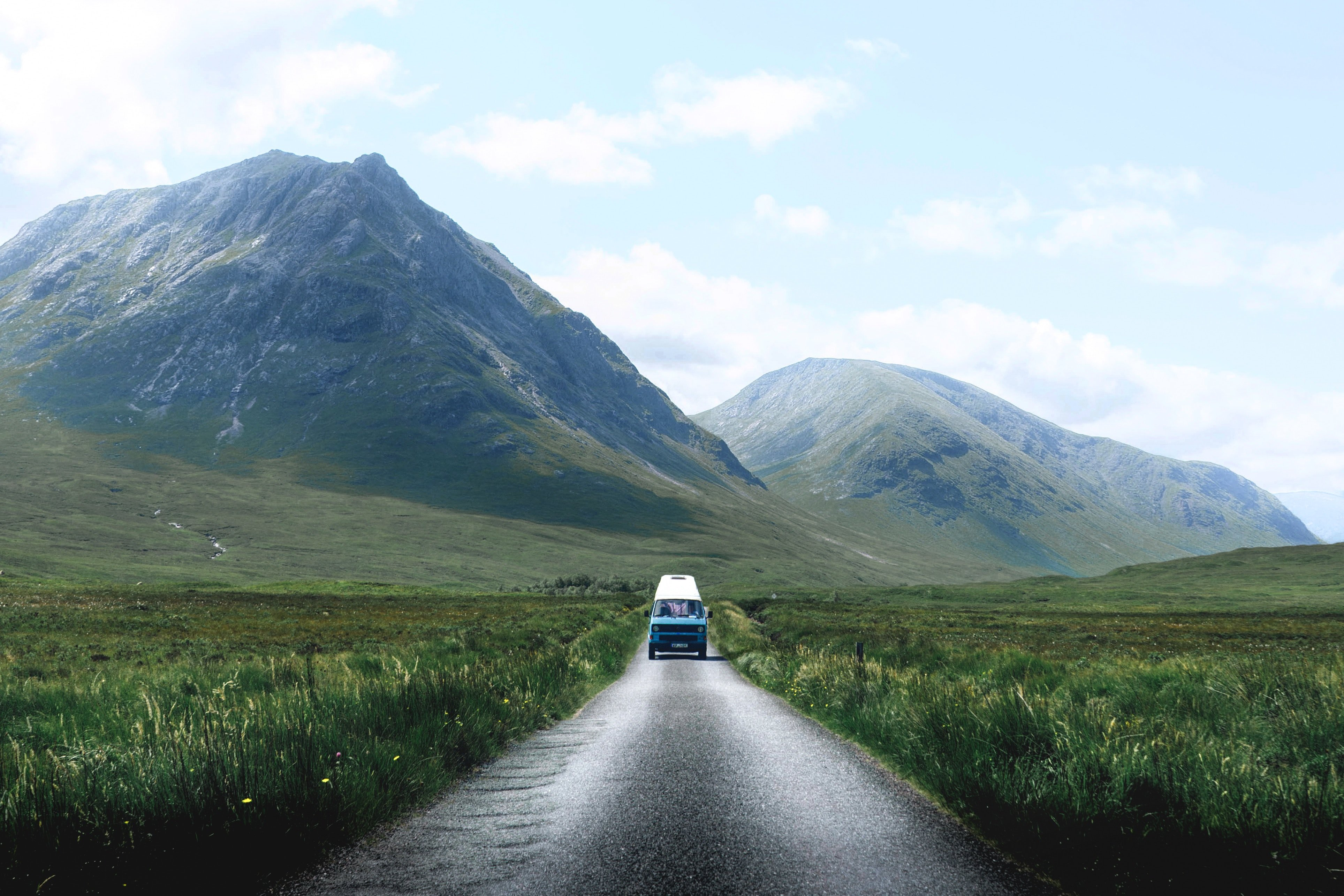 van driving on a road by mountiains