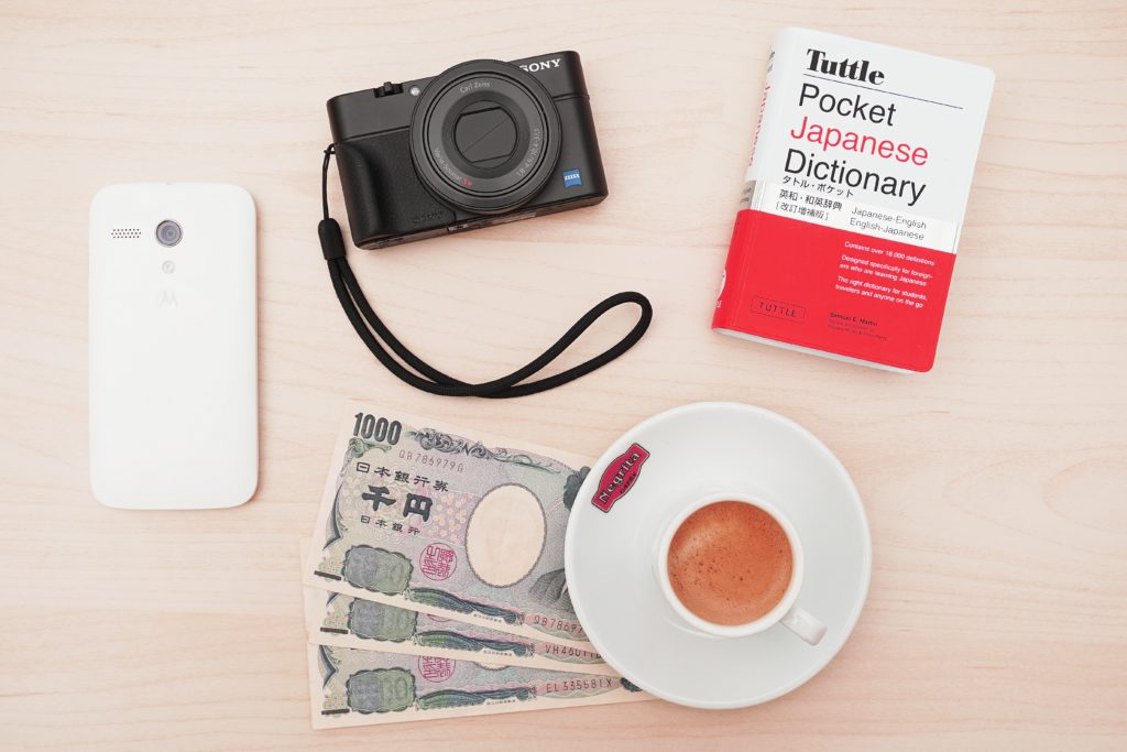 table with japanese dictionary, camera, and money