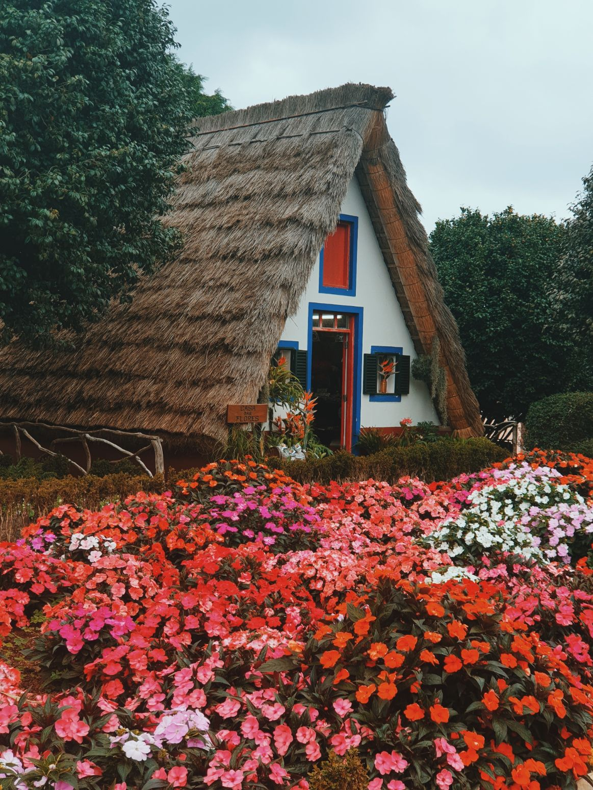 a-frame cottage with a beautiful red blooming garden in front of it