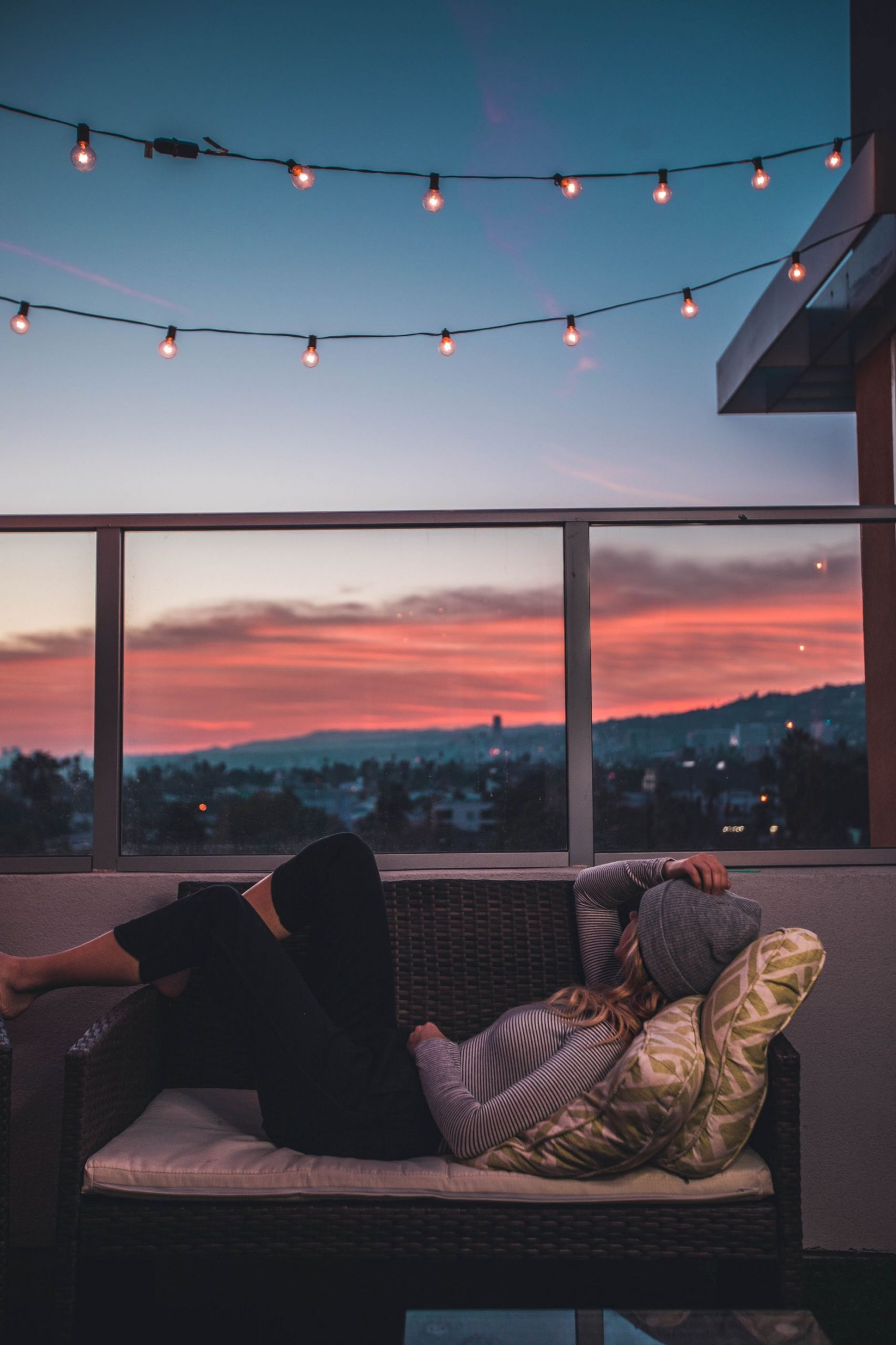 girl on a couch on a balcony at sunset