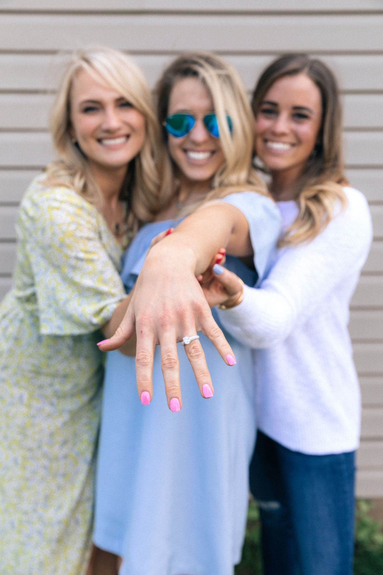 girl showing off her engagement ring with friends