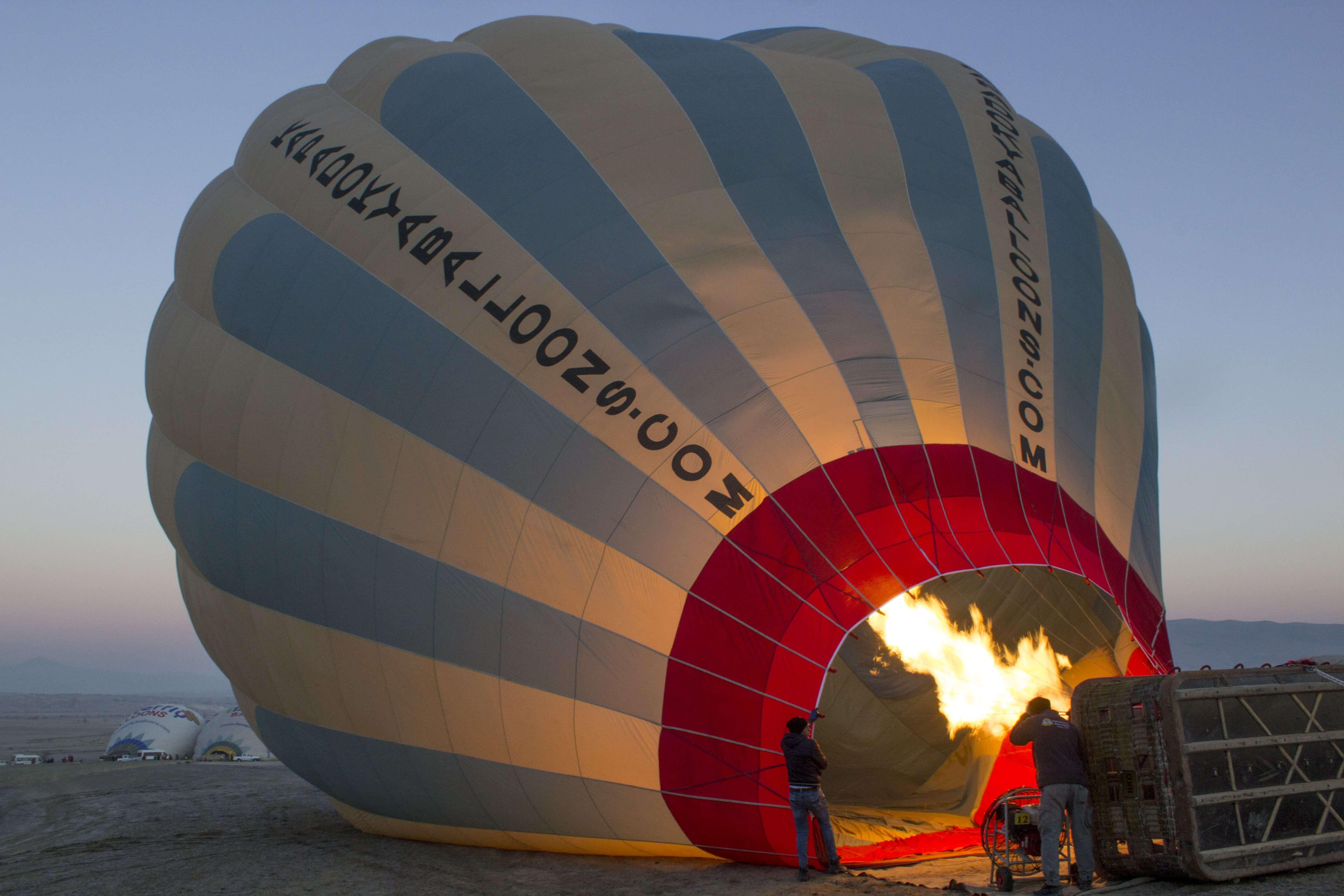 blowing up a hot air balloon at sunrise