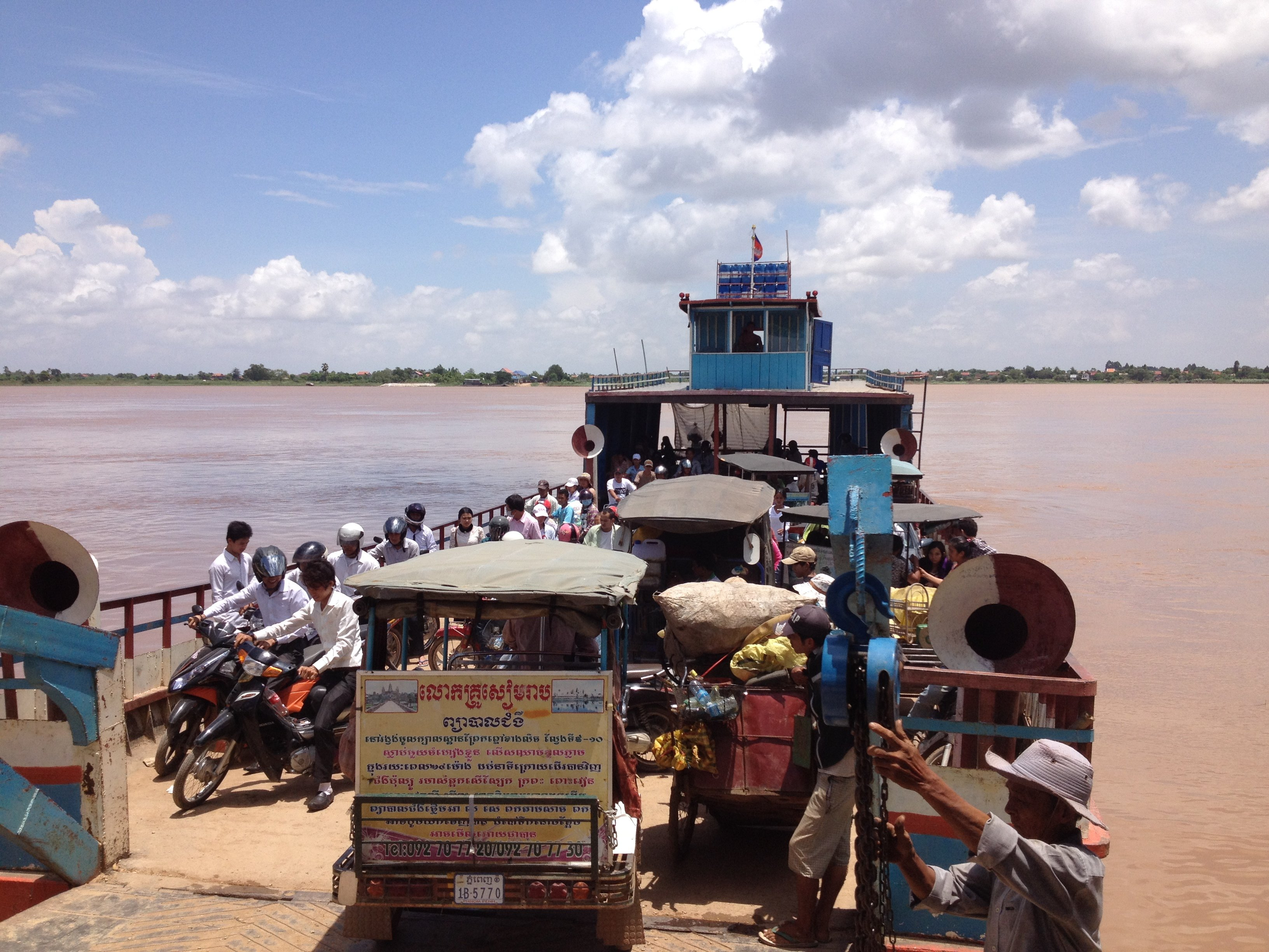 Tuk Tuks and other vehicles riding a ferry to cross the Mekong River