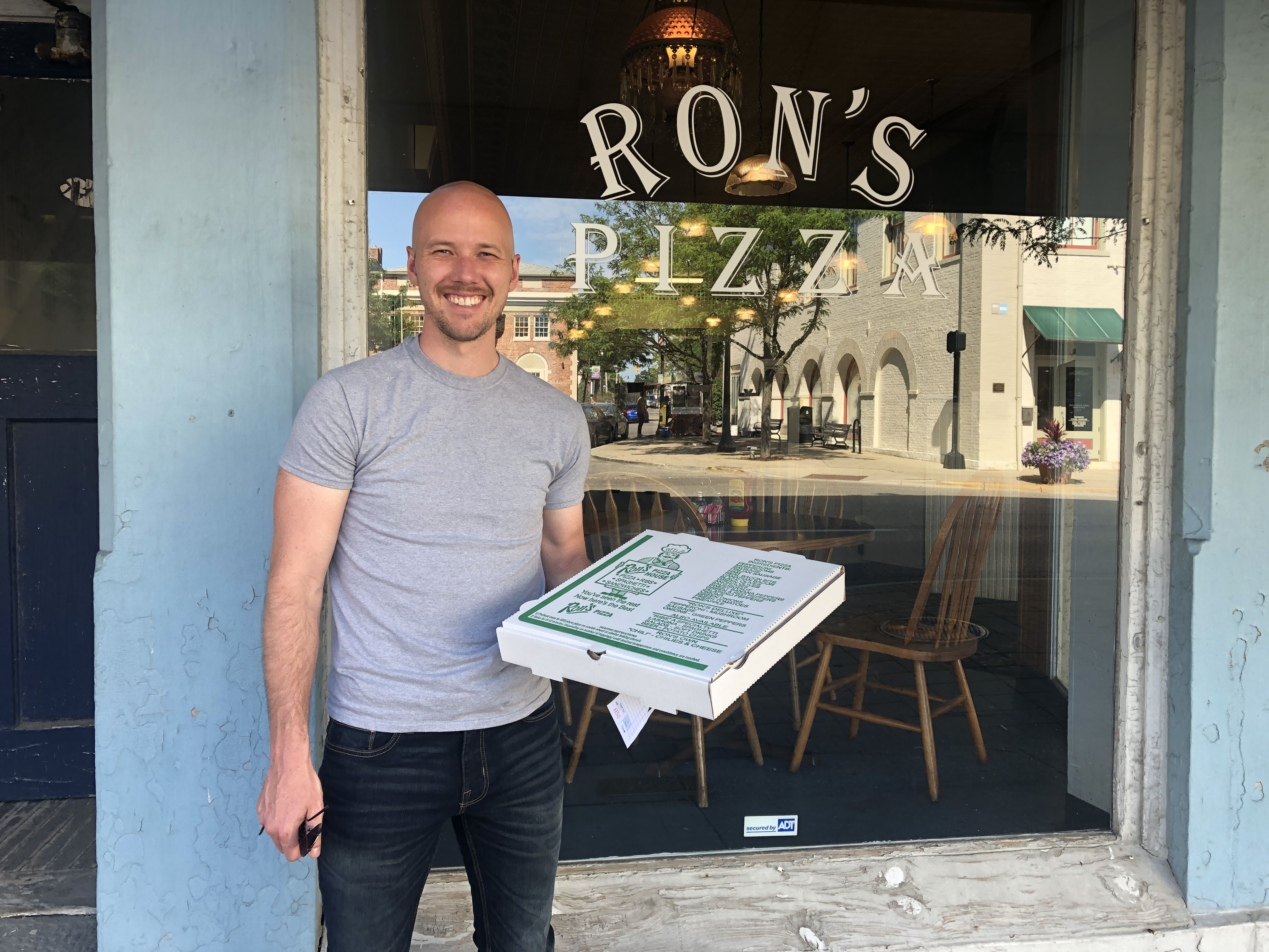 man holding pizza in front of Ron's