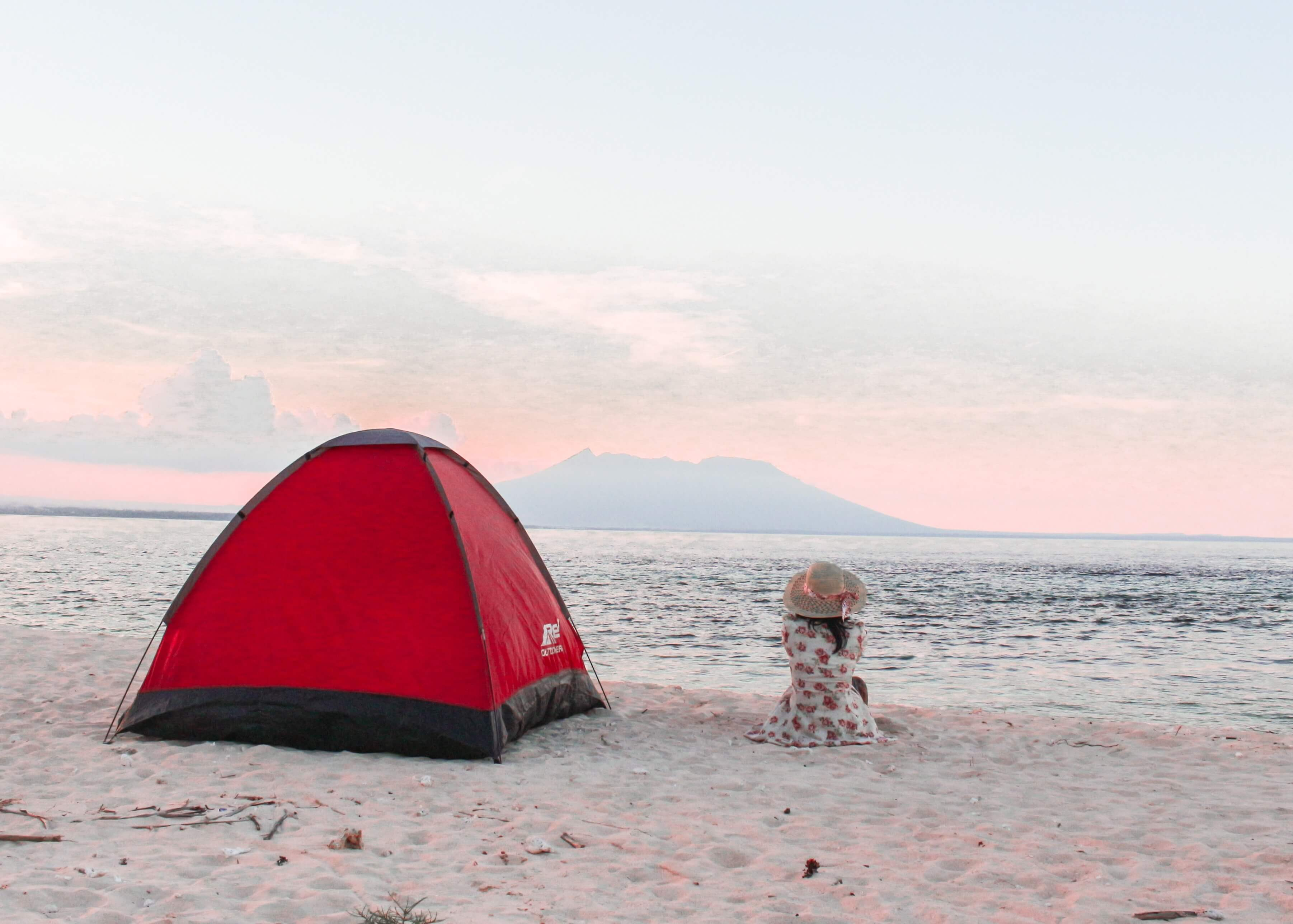 girl watching the sunrise while camping on the beach