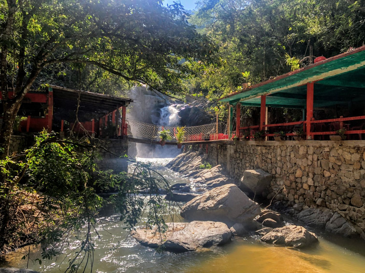 Quimixto waterfall with a red and green restaurant in front of it