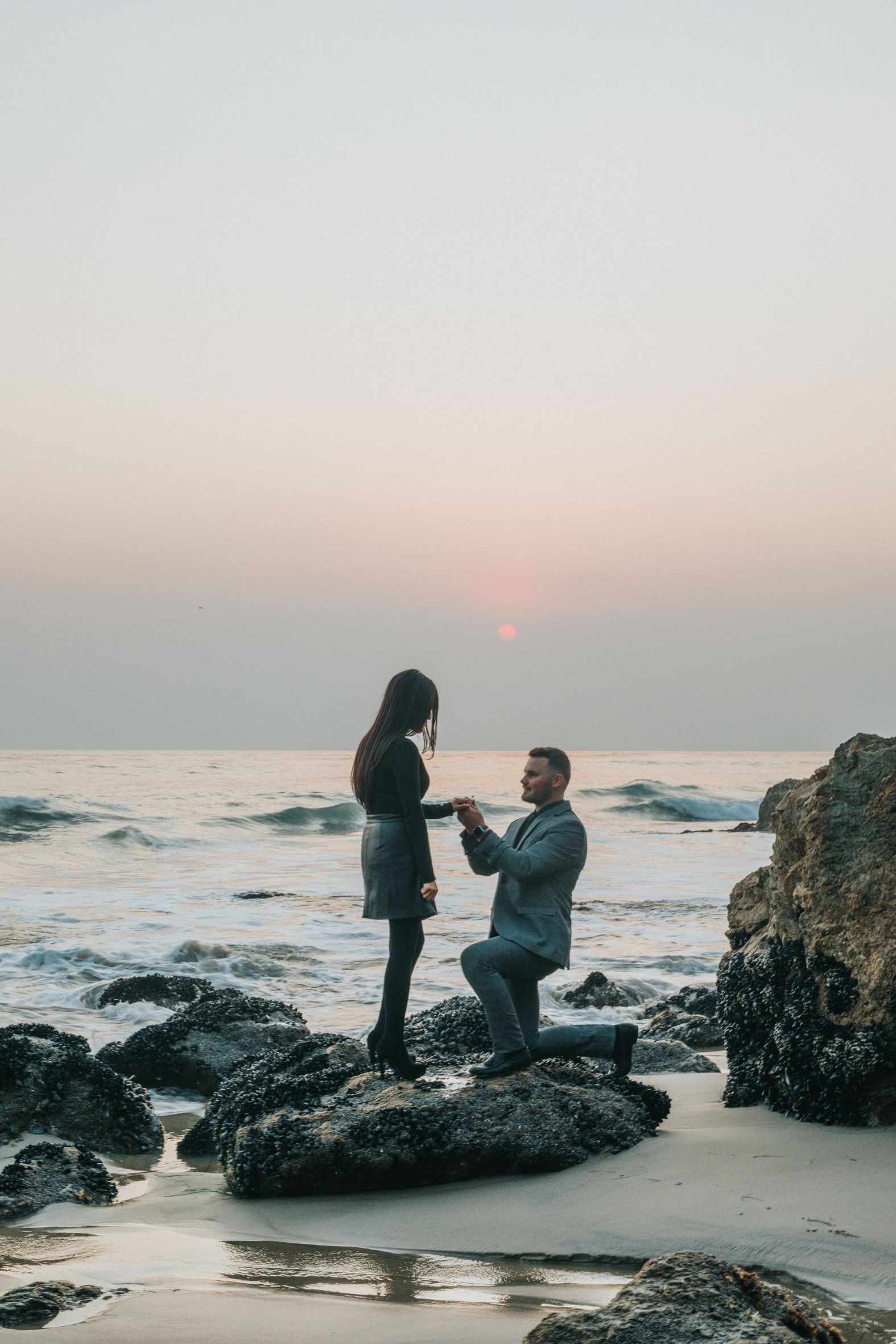 man proposing at the beach at sunset