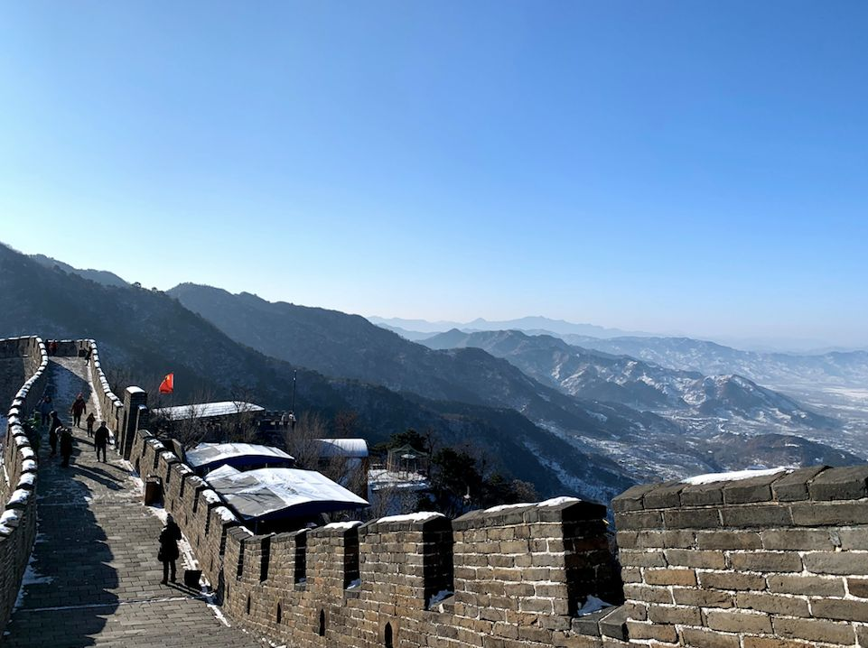 walking along the great wall of China in the winter with a view of the mountains