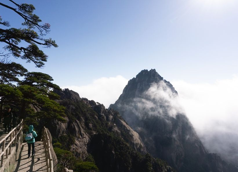 mountain and bridge walkway while hiking in Huangshan, China