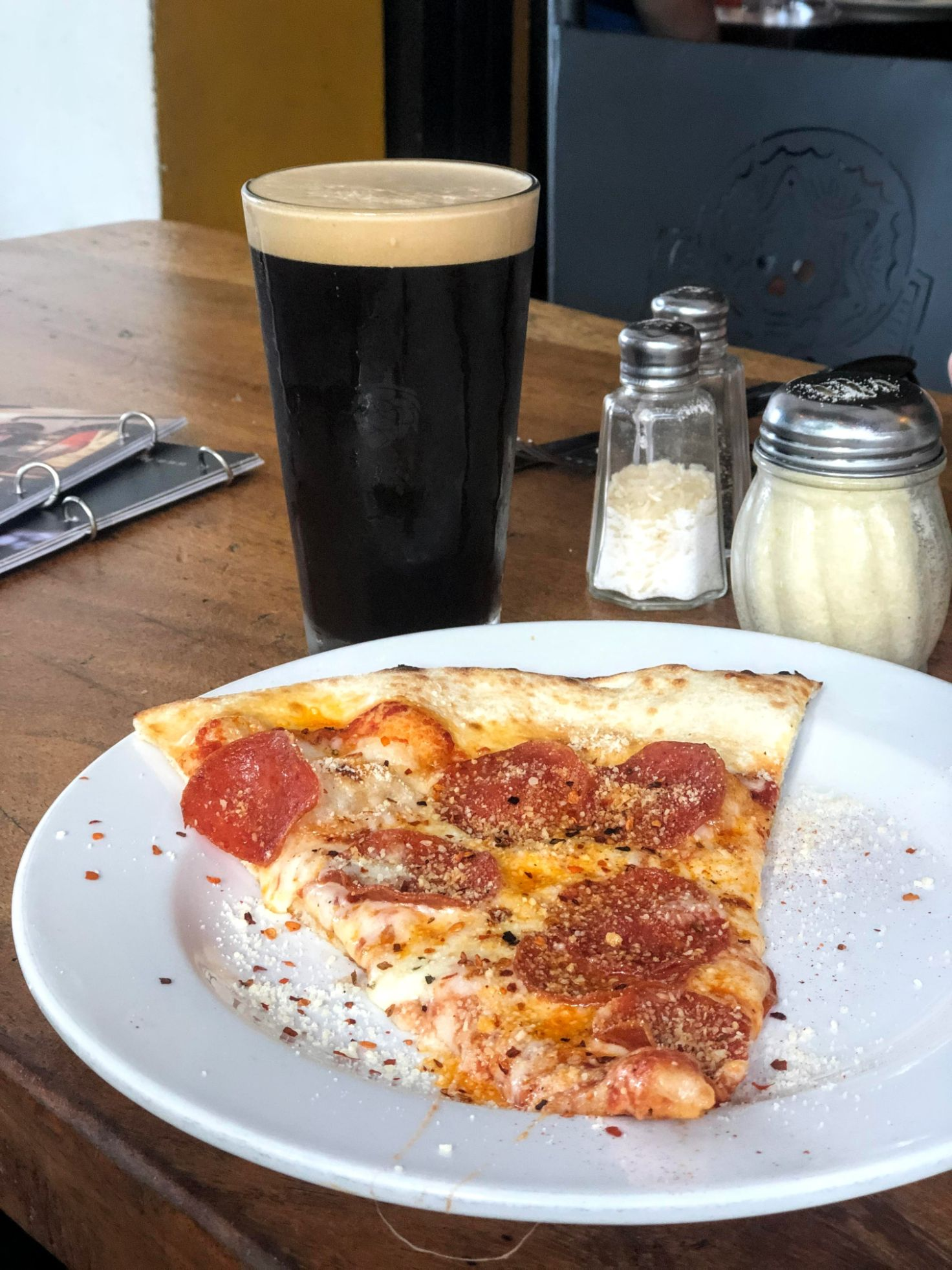 Dark stout and slice of pepperoni pizza at Muertos Brewing