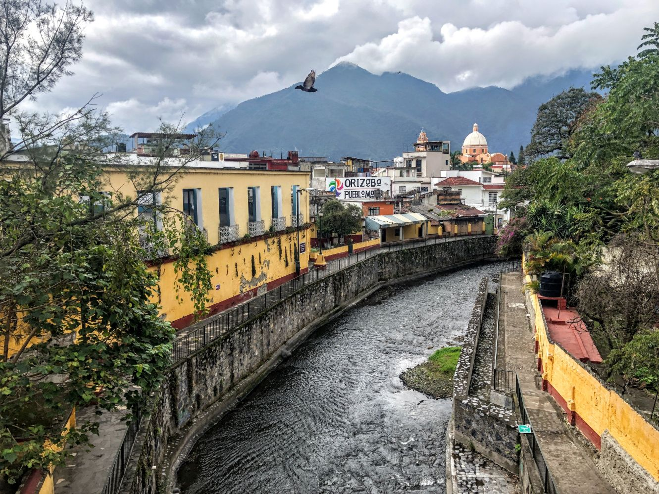 Orizaba river running through the colorful town center with mountains in the background