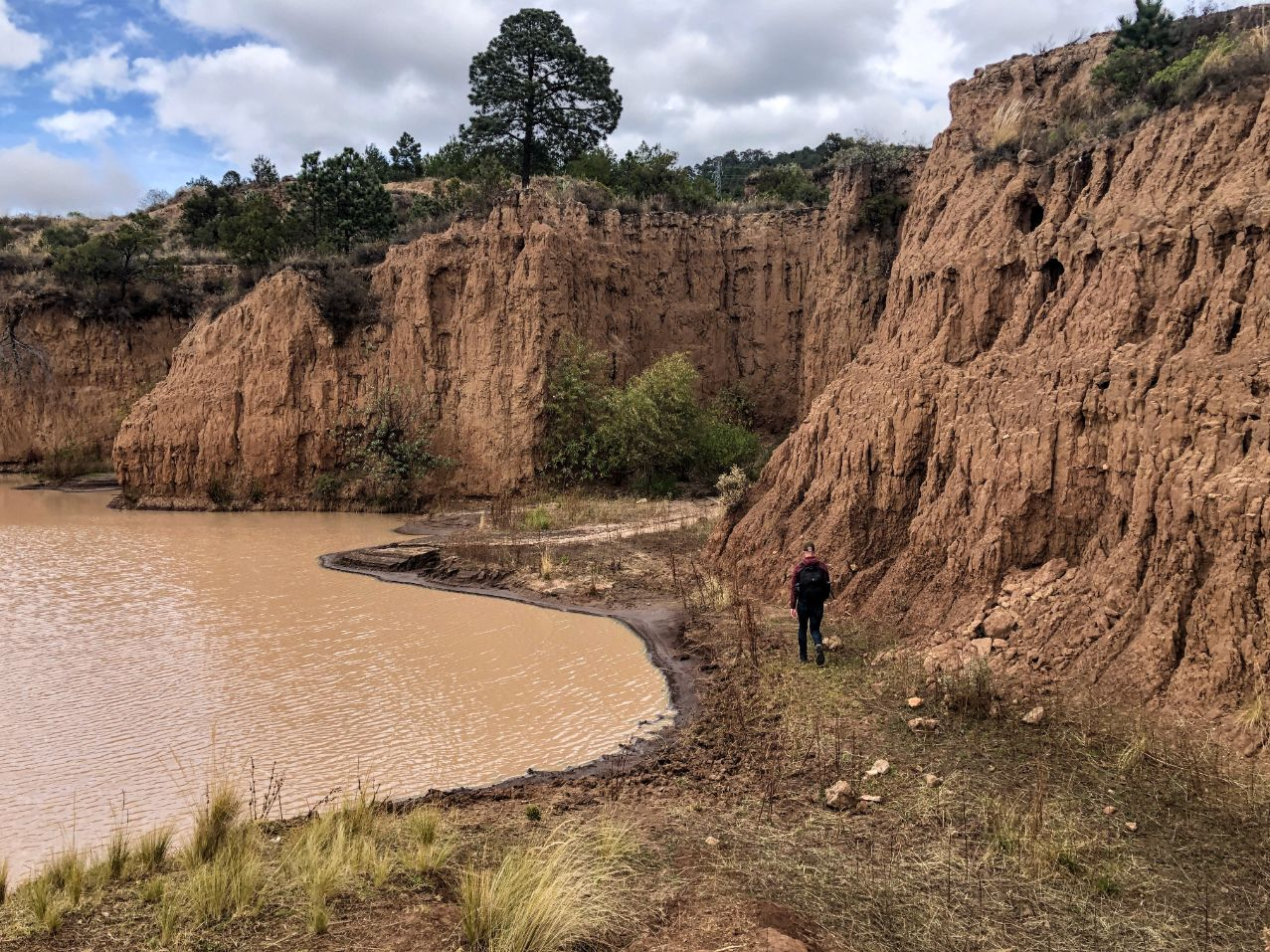 man hiking between a lake and brown canyon wall
