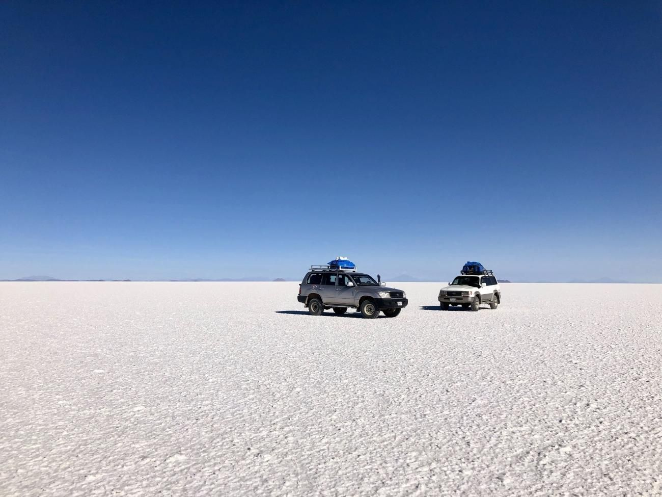 two trucks on an endless expanse of white in the Bolivian salt flats