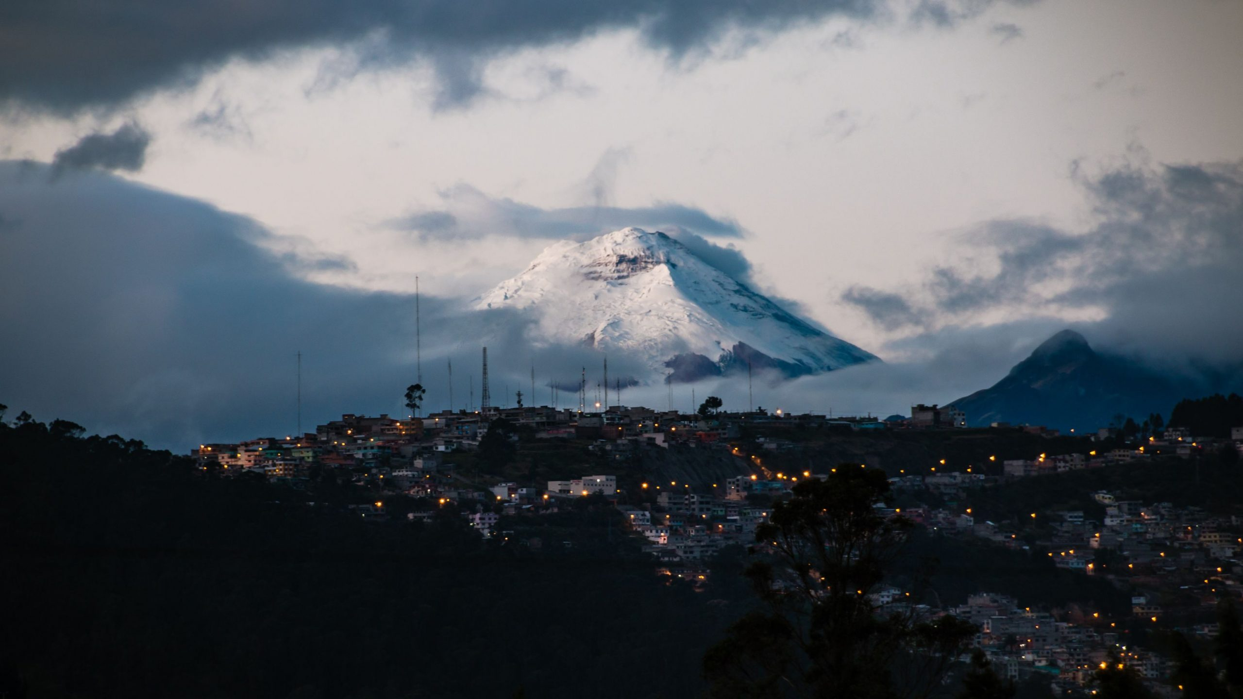 Quite, Ecuador cityscape at night with a snow covered mountain