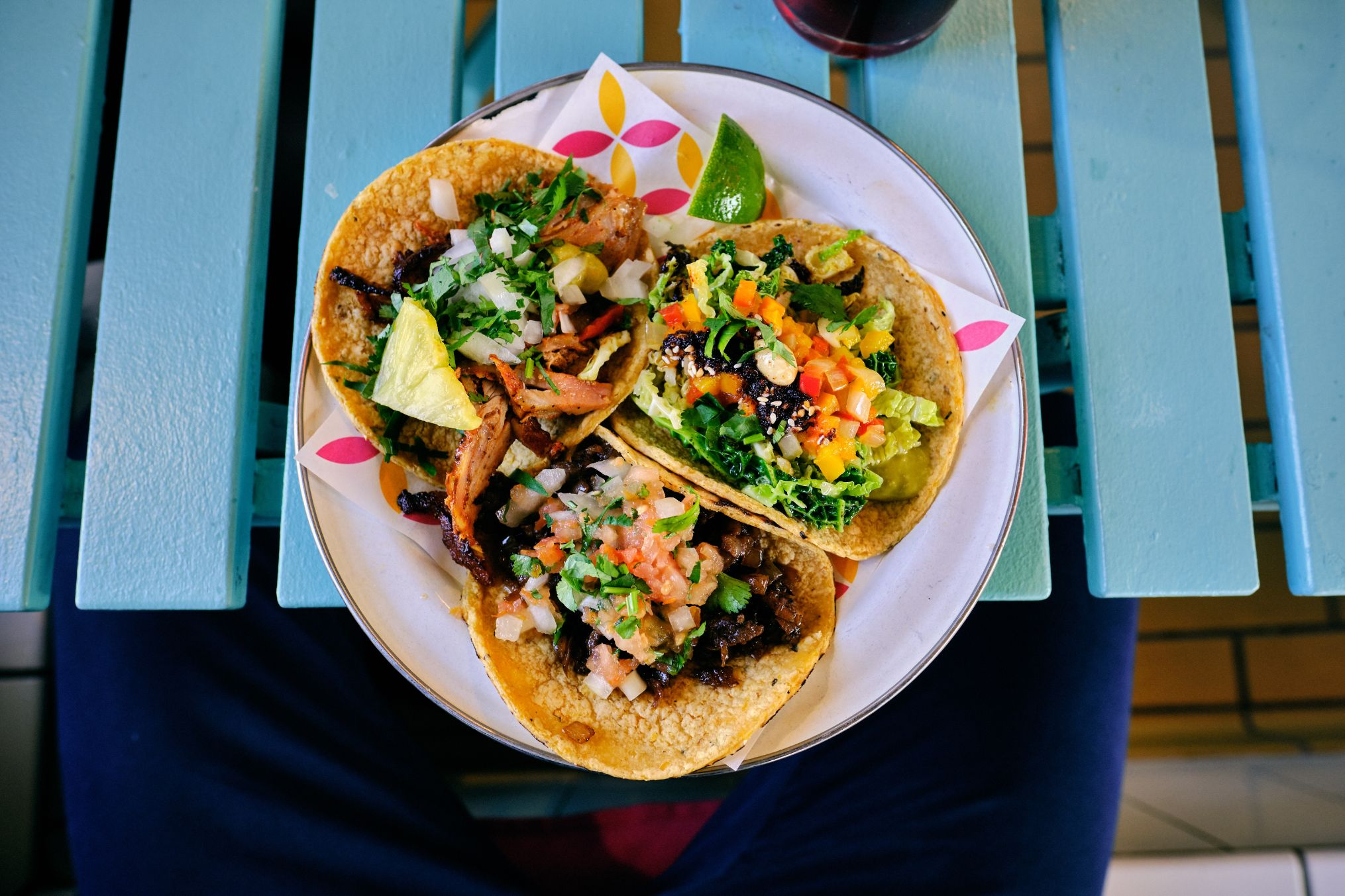 plate of three tacos on a blue table