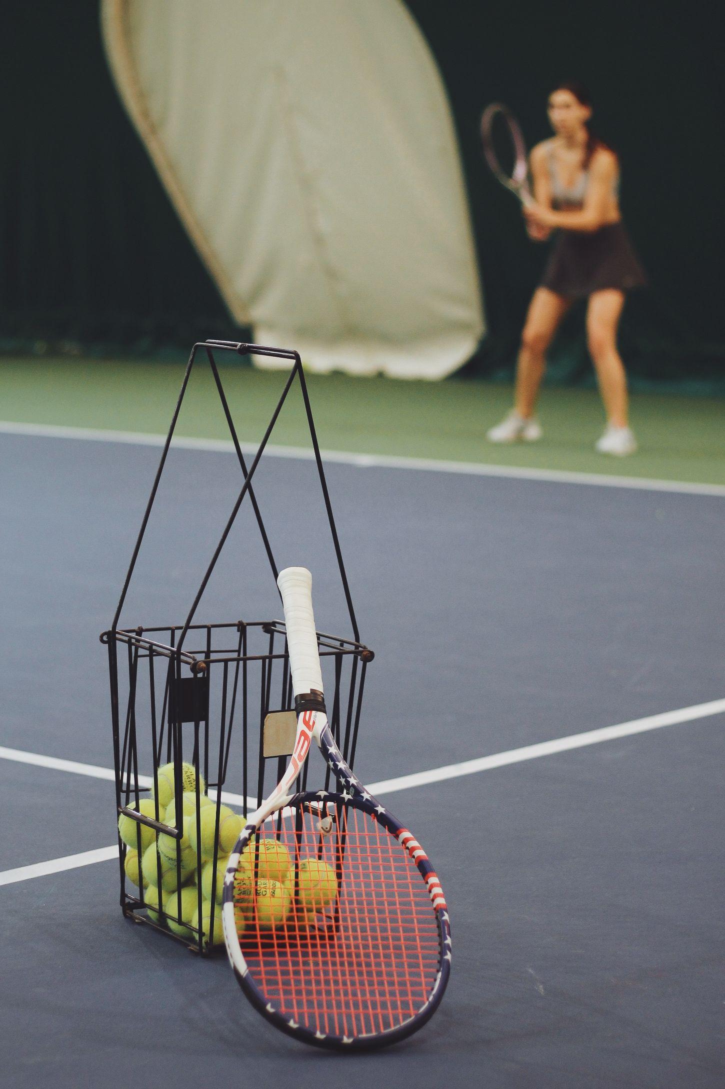 tennis balls and racket on a tennis court