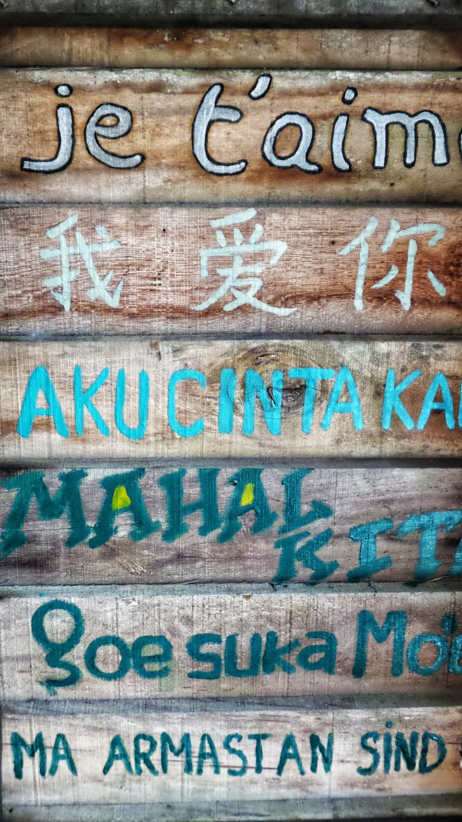 wooden sign painted with phrases in different languages
