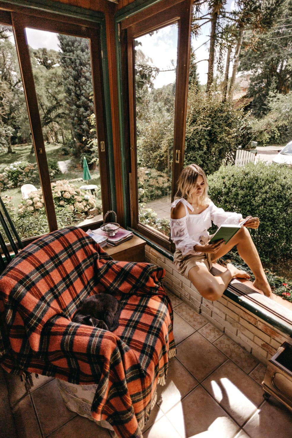 girl reading a book on a sunny balcony