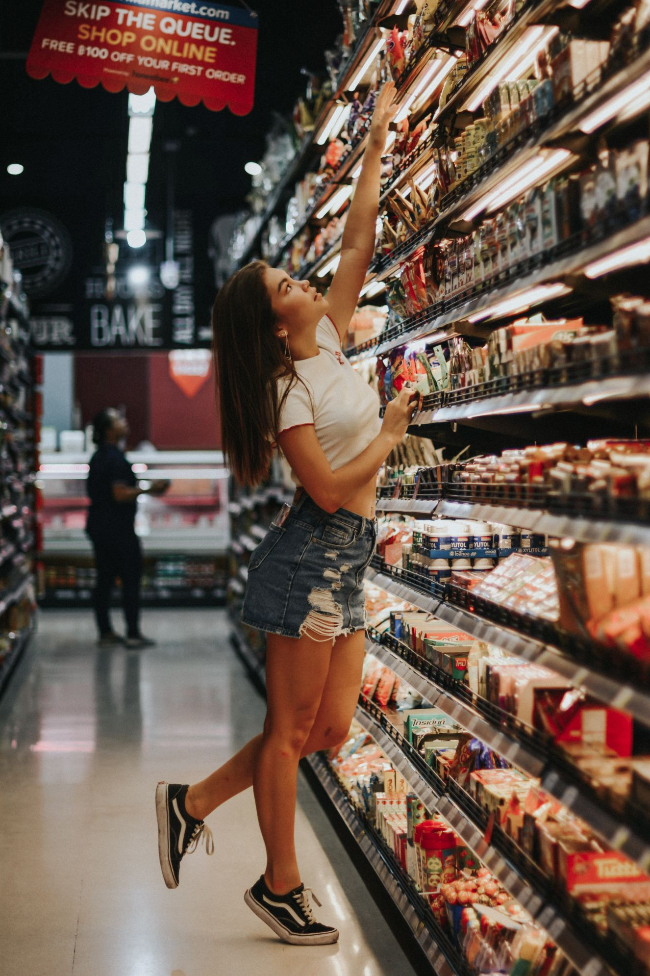 girl reaching for food in a grocery story