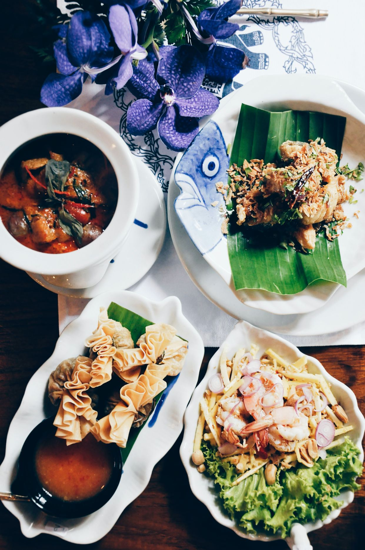 Thai food spread on the table with dishes of dumplings, curry, and more